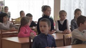 School kids sit at desks. CHAPAEVSK, SAMARA REGION, RUSSIA - FEBRUARY 02, 2018: School kids of elementary school sit at desks in the classroom. College of the stock footage