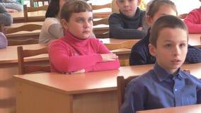 School kids sit at desks. CHAPAEVSK, SAMARA REGION, RUSSIA - FEBRUARY 02, 2018: School kids of elementary school sit at desks in the classroom. College of the stock video