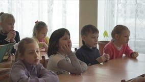 School kids sit at desks. CHAPAEVSK, SAMARA REGION, RUSSIA - FEBRUARY 02, 2018: School kids of elementary school sit at desks in the classroom. College of the stock video footage