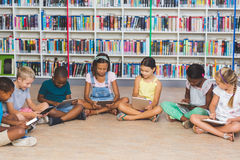 School kids sitting on floor using digital tablet in library Royalty Free Stock Photos