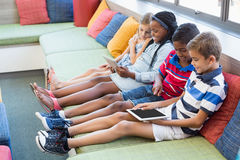 School kids sitting on sofa and using digital tablet in library. At school Royalty Free Stock Photography