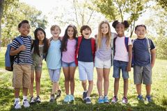 School kids stand embracing in a row outdoors, full length royalty free stock photo