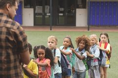 School kids standing in a queue in the schoolyard. Front view of school kids standing in a queue in the schoolyard with their back teacher in foreground royalty free stock image