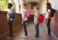 School kids standing in school corridor. Side view of school kids standing in school corridor Stock Image