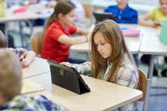 School kids with tablet pc in classroom stock images