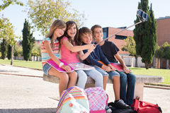 School kids taking selfies. School kids talking photos with a selfie stick royalty free stock image