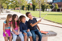 School kids taking selfies. School kids talking photos with a selfie stick stock images