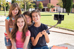 School kids taking selfies. School kids talking photos with a selfie stick royalty free stock photos