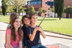 School kids taking selfies. School kids talking photos with a selfie stick royalty free stock images