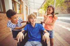School kids talking to a boy on wheelchair. In school corridor Royalty Free Stock Photo