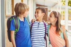 School kids talking to each other in school corridor. Smiling school kids standing in corridor and talking to each other at school royalty free stock photo