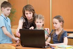 School kids and teacher at laptop in the classroom. School children and teacher at laptop in the classroom Royalty Free Stock Images