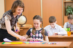 School kids and teacher at lesson. Schoolkids work at labour lesson. Teacher controlling pupil Royalty Free Stock Image