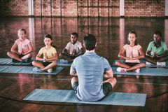 School kids and teacher meditating during yoga class royalty free stock photo