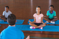 School kids and teacher meditating during yoga class. In basketball court at school gym Stock Photos