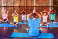 School kids and teacher meditating during yoga class. In basketball court at school gym Royalty Free Stock Photography
