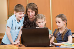 School kids and teacher using laptop at lesson Stock Image