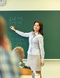 School kids and teacher writing on chalkboard Stock Photo