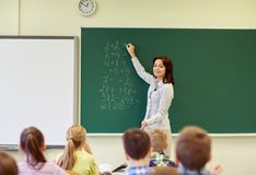 School kids and teacher writing on chalkboard. Education, elementary, teaching, math and people concept - group of school kids and teacher writing mathematic stock photography