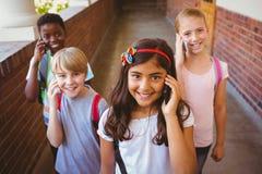 School kids using cellphones in school corridor. Portrait of smiling little school kids using cellphones in school corridor Stock Photos