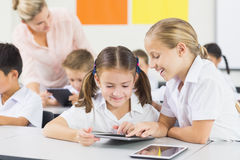 School kids using digital tablet in classroom Stock Photography