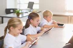 School kids using digital tablet in classroom. At school Royalty Free Stock Photography