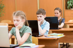 School kids using laptop at lesson Stock Photography