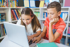 School kids using a laptop in library. At school Stock Photo