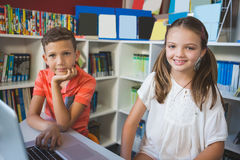 School kids using a laptop in library. Portrait of school kids using a laptop in library at school Royalty Free Stock Photography