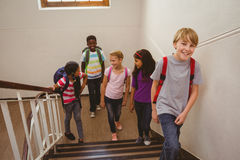 School kids walking up stairs in school. Full length of school kids walking up stairs in the school Royalty Free Stock Images