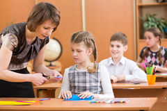 School kids work at lesson. School kids work at labour lesson. Teacher helping pupil Royalty Free Stock Photography