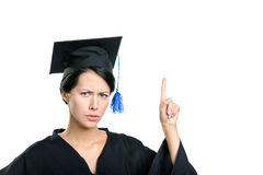 School leaver making the attention gesture. Graduating student in black academic gown and cap making the attention gesture, isolated stock photography