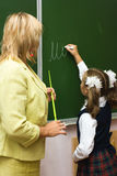 At a school lesson. The schoolgirl writes a chalk on a board a word, the teacher attentively looks on a board Stock Photography