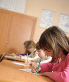 School lesson. Cute schoolchildren are writing using pencils during lesson Stock Photography
