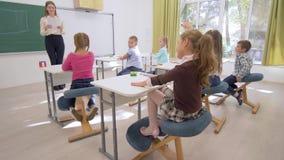 School lesson, young teacher near board conducts cognitive lesson for Smart children at desk in classroom of school. School lesson, young teacher near board stock video