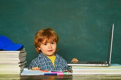 School lessons. Kid is learning in class on background of blackboard. Teachers day. Home schooling. School and education. Concept stock photos