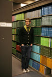 At School Library. Male College student wearing glasses and tie standing in front of books Royalty Free Stock Photo