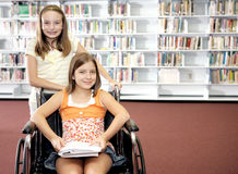 School Library - Two Girls. Two school girls at the library.  One is in a wheelchair Royalty Free Stock Photography