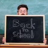School life full of stress. Teacher peeking out of blackboard. Educator hiding behind blackboard. Man scared beginning. School year. Teacher or school principal stock images