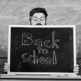 School life full of stress. Teacher peeking out of blackboard. Educator hiding behind blackboard. Man scared beginning stock photos