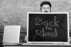 School life full of stress. Teacher or school principal welcomes inscription back to school. Teacher peeking out of. Blackboard. Educator hiding behind stock image