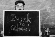 School life full of stress. Teacher or school principal welcomes inscription back to school. Educator hiding behind. Blackboard. Man scared beginning school stock images
