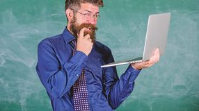 School lifehack. Hipster teacher wear eyeglasses and necktie holds laptop surfing internet. Teacher bearded cunning man. Modern laptop surfing internet stock photo
