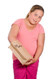 School Lunch. A preteen girl reaching into her lunch bag to get her food out, isolated against a white background - artificial name on the lunchbag Stock Photography
