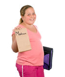 School Lunch. A young girl holding up her lunch for school, isolated against a white background with a fake name on the lunch bag Stock Photo