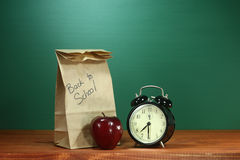 School Lunch, Apple and Clock on Desk at School Royalty Free Stock Images