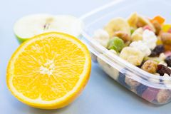 School lunch box. Bread, apple, candies, baby corns, carrot and tomatoes in green plastic container. Top view, blue background stock photography