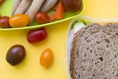 School lunch box. Bread, candies, baby corns, carrot and tomatoes in green plastic container. Top view, yellow background stock photo