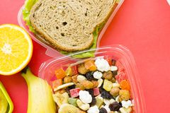 School lunch box. Bread, orange, baby corns, carrot and tomatoes in green plastic container. Top view, red background royalty free stock photography