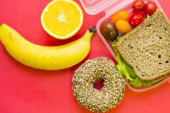School lunch box. Bread, orange, baby corns, carrot and tomatoes in green plastic container. Top view, red background royalty free stock image